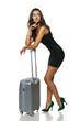 Woman standing leaning on silver suitcase looking to the side