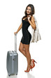 Woman with jacket over shoulder standing with silver suitcase