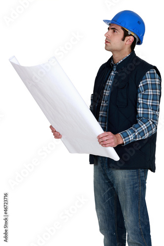 Construction worker verifying a building drawing