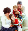 grandparents reading books to beautiful grandchildren