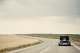 Classic Car in a Country Road - 46728738