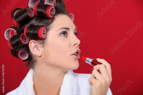 woman with curlers in her hair putting lipstick