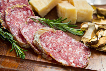 parmesan cheese and salami on wooden board