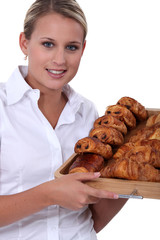 female baker bringing croissants on a plate