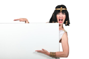 Woman dressed as Cleopatra pointing to a blank sign