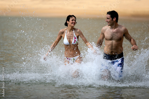 Couple running through water at the beach