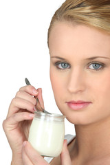 Blond woman eating yogurt