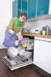 Frau beim Geschirrspüler einräumen