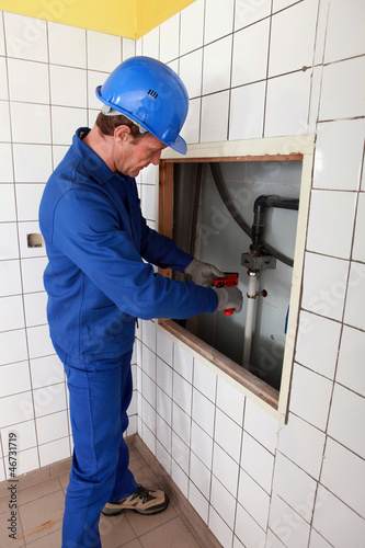 Plumber working in a tiled room