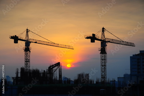 Leinwanddruck Bild Crane construction at sunrise