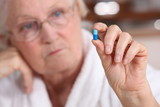 An old woman taking a pill.
