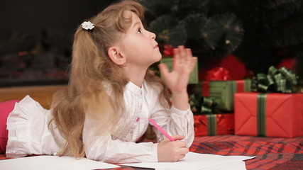 Little girl drawing her wishes under a Christmas tree