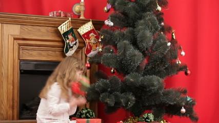 Children choosing presents under a Christmas tree