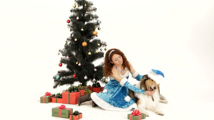 The Snow Maiden seating under a Christmas tree with a dog