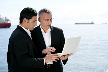 Businessmen outdoors working on laptop