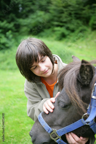 boy caressing a pony