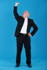 mature man in suit touching ceiling against blue background