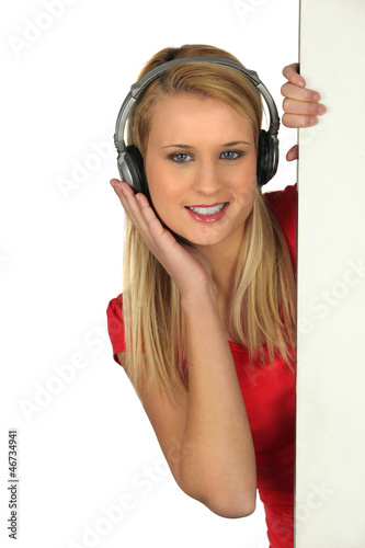 Girl with earphones hidden behind a panel