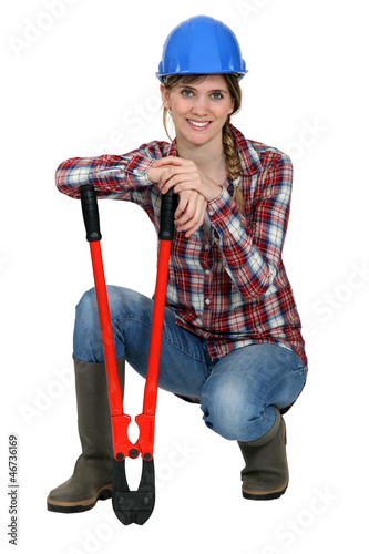 Woman kneeling by bolt cutters