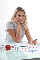 Blond woman working with financial graphs