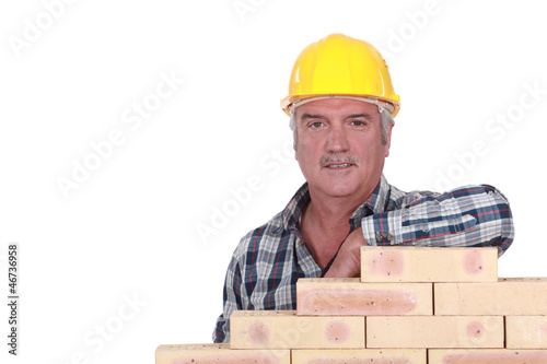 Artisan leaning on stack of bricks