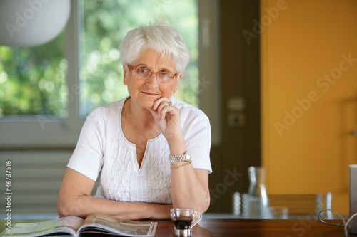 Grandmother reading magazine in the kitchen