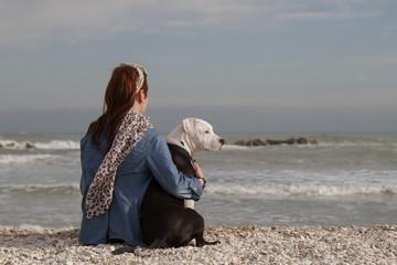 beautiful young woman embracing dog looking at the sea