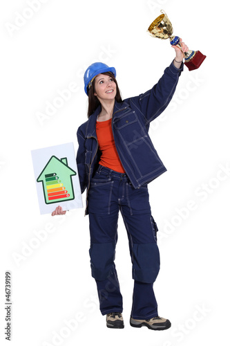 A female construction worker holding a trophy cup.