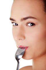 Smiling woman with spoon in her mouth
