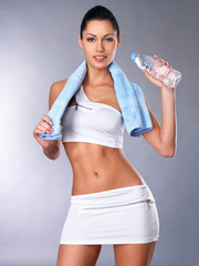 Portrait of a healthy woman with  bottle of water and towel.