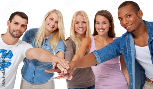5 junge Leute legen symbolisch die Hände aufeinander