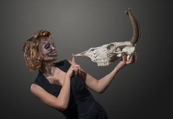 Woman with cow's skull in her hands, face to face