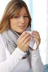 Erkältete Frau mit Papiertaschentuch