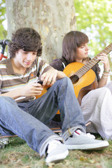 Two teens with guitar sat by tree