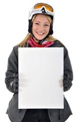 Junge Frau in Skianzug hält leeres Schild