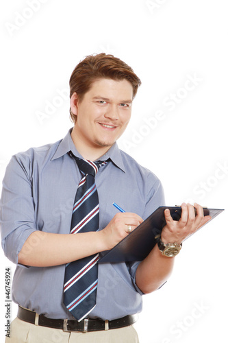 Caucasian businessman writing notes and smiling at the camera