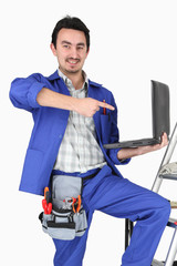 Plumber with a laptop and various tools of the trade