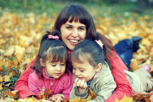 Young happy mother and her daughters play in autumn park