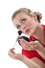 Blond woman applying blusher