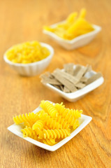 Several small bowls of raw pasta, selective focus