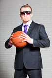 Angry business man with basketball. Wearing dark sunglasses.