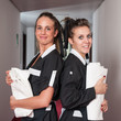 Two chambermaid women portrait in a hotel.