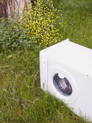 Washing machine abandoned in the grass