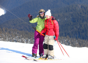 Young female skier and snowboarder on ski-lift