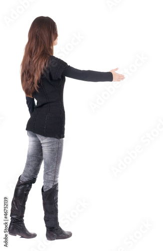 back view of businesswoman  reaches out to shake hands.