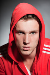 Fashion portrait of urban young man wearing red hoody jacket.