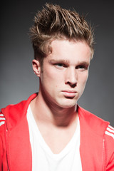 Fashion portrait of sportive young man wearing red jacket.