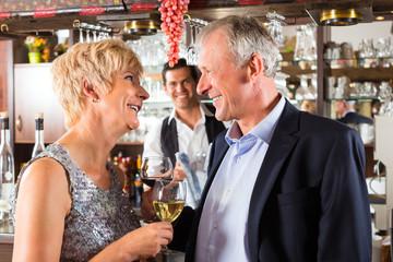 älteres Paar an der Bar mit Weinglas in Hand