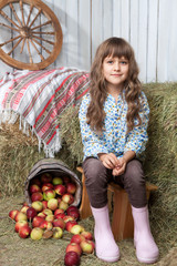 Portrait of girl villager near pail with  apples in hayloft