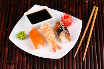 delicious sushi served on plate on bamboo mat